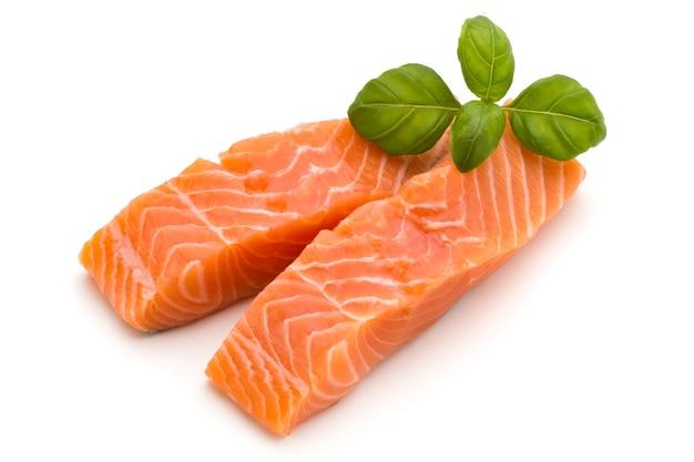 Свежее филе лосося с базиликом на белом фоне