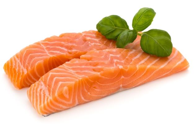 Филе свежего лосося с базиликом на белой поверхности.