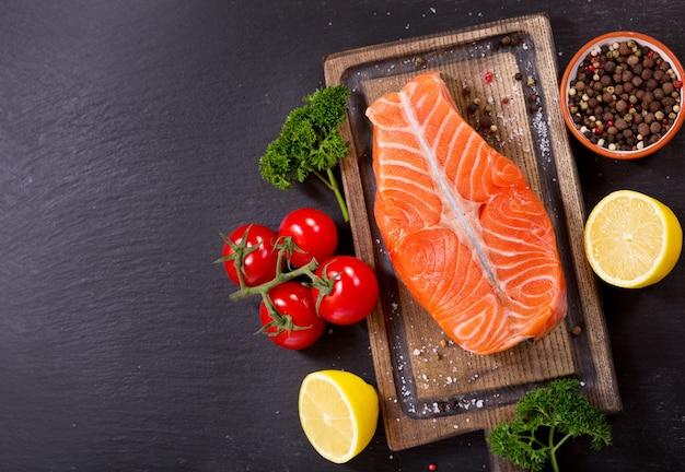 Свежее филе лосося с ингредиентами для приготовления на деревянной доске, вид сверху