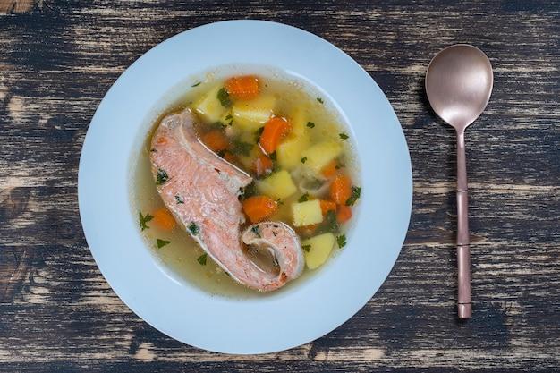 Рыбный суп из свежего лосося с морковью, картофелем и зеленью в белой тарелке, крупным планом. вкусный ужин - ухи с лососем.