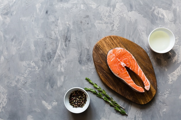 Fresh salmon fish steak with spices on gray stone background