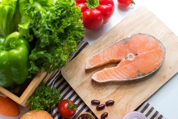 스테이크 샐러드를 요리하기 위해 야채와 함께 신선한 연어 생선. 건강하고 다이어트 식품입니다.