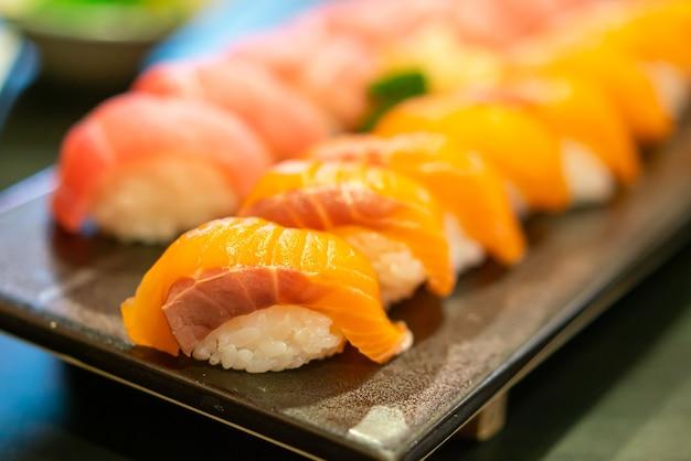 Сырые суши со свежим лососем на тарелке - стиль японской кухни