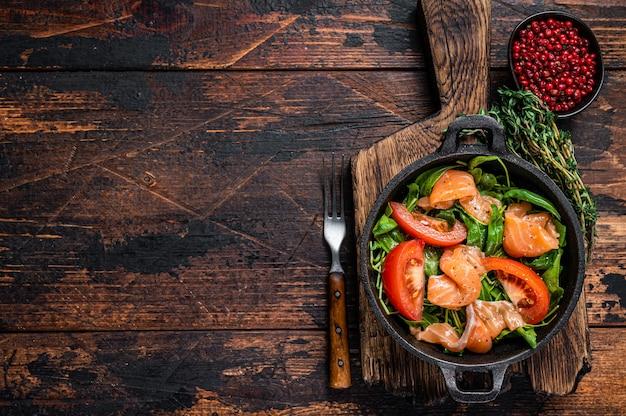 Салат из свежего лосося с рукколой, помидорами и зелеными овощами. темный деревянный стол. вид сверху.