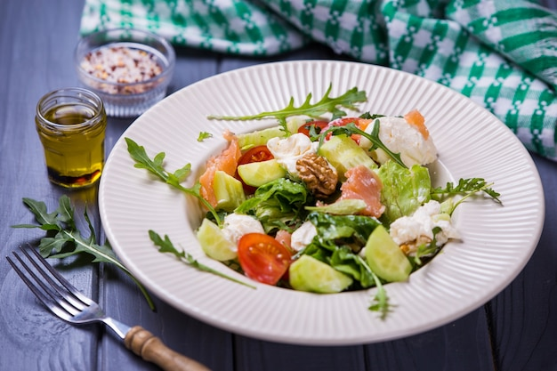 Fresh salmon salad with red tomatoes, soft cheese,cucumber,nuts and arugula