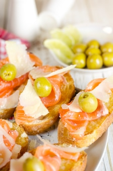 Fresh salmon sandwich with cheese and olives