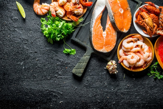 Fresh salmon steak on a cutting board with shrimp, crayfish and parsley. on black rustic