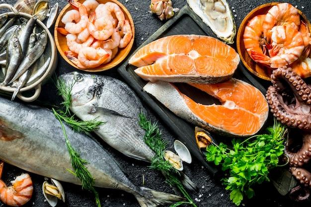 Свежий стейк из лосося с различными морепродуктами и травами на черном деревенском столе.