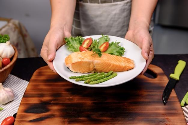 新鮮なサーモンステーキとサラダ。コロナウイルス中に家にいるときの食事と健康食品を調理するためのオンライン学習。