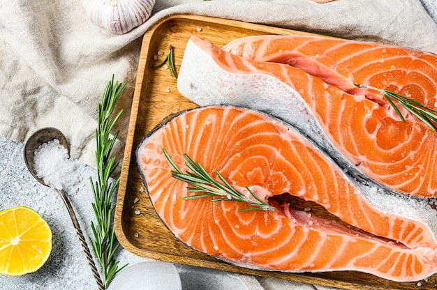 Fresh salmon steak on wooden tray with spices. atlantic fish. gray background. top view