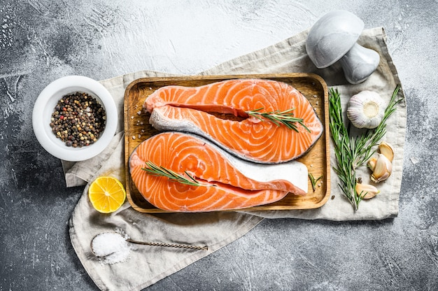 Fresh salmon steak on wooden tray with spices. atlantic fish. gray wall. top view