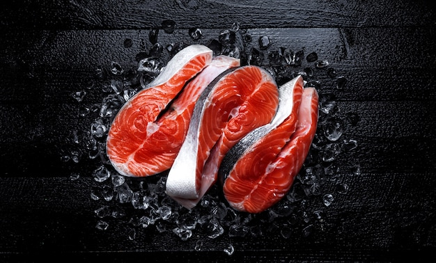 Fresh salmon steaks on black wooden surface