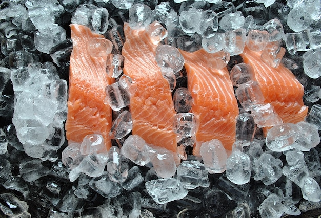 Fresh salmon steaks . fresh salmon steaks on ice and black background