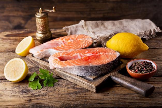 Свежие стейки из лосося с ингредиентами для приготовления на деревянном столе