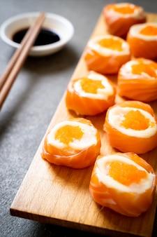 마요네즈와 새우 계란을 곁들인 신선한 연어 스시 롤-일본식 스타일
