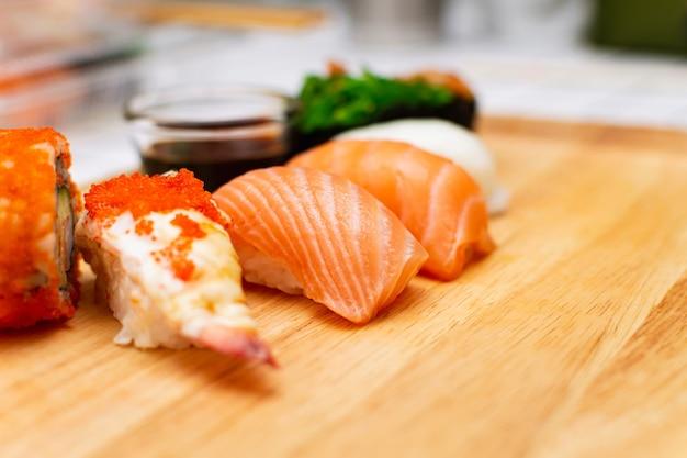 Суши из свежего лосося с креветками и тобико (яйца летучей рыбы) в деревянной тарелке.