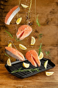 Fresh salmon or trout fish with spices and herbs falling on grill pan on wooden background. flying food and levitation concept.