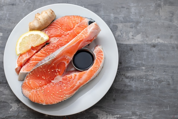 Fresh salmon with lemon ginger and soy sauce on white plate on grey wood background