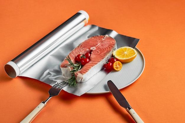 Свежий лосось с лимоном в фольге, готовый для приготовления в духовке на оранжевом фоне.