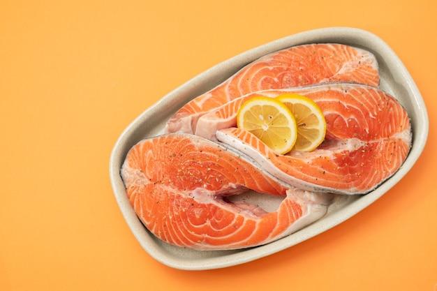 Свежий лосось с лимоном на блюде на апельсиновом столе