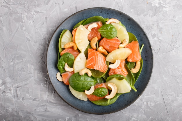 Fresh salmon with pineapple, spinach and cashew in blue ceramic plate on a gray concrete.