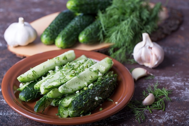 Fresh-salted cucumbers on a plate with dill and garlic