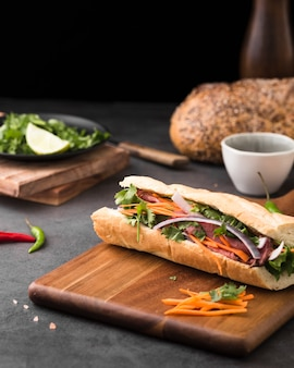 Fresh sandwich on chopping board with carrots