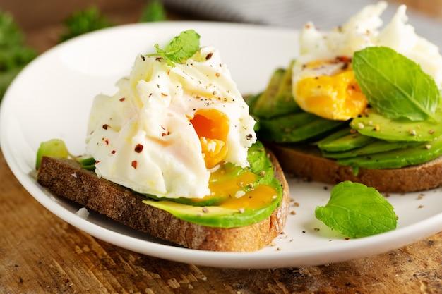 아보카도와 빵에 데친 계란 신선한 샌드위치. 접시에 제공됩니다. 확대