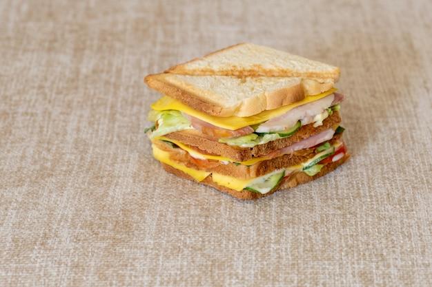 베이지색 냅킨에 치즈, 허브, 토마토, 오이, 베이컨을 넣은 신선한 샌드위치.