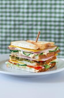 치즈, 허브, 토마토, 오이, 베이컨 흰색 테이블에 신선한 샌드위치