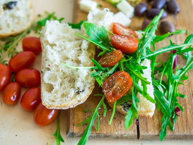 Fresh sandwich with cherry-tomatoes, goat cheese, olives and arugula on a wooden kithchen board