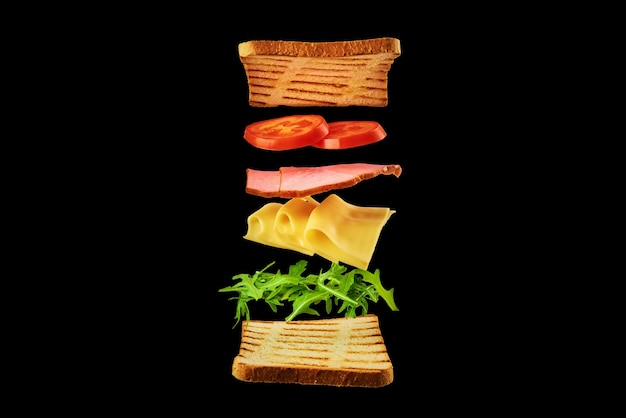 Fresh sandwich with flying ingredients on the black background isolated. fly food concept