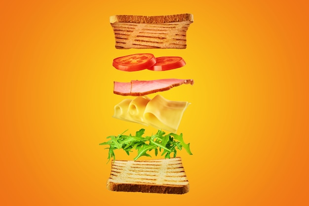 Fresh sandwich with flying ingredients on the yellow