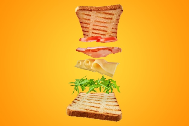 Fresh sandwich with flying ingredients on yellow