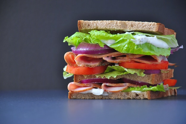 Fresh sandwich with ham,tomatoes,lettuce,onion on black surface