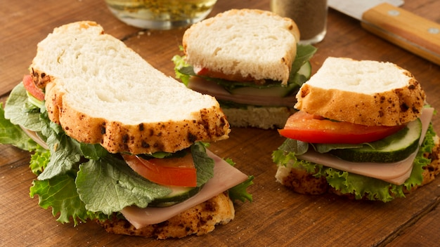 Fresh sandwich with salami and vegetables on table