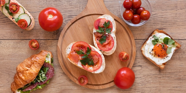Fresh sandwiches composition on wooden background