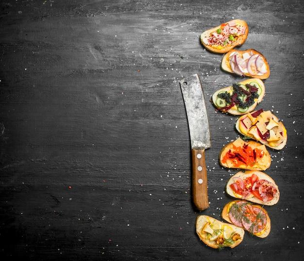 Свежие бутерброды из морепродуктов с лососем, икрой, овощами сало на черной доске.