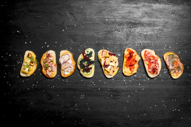 黒い黒板にサーモン、キャビア、ベーコンド野菜を添えたシーフードの新鮮なサンドイッチ。