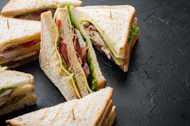 黒の背景に、食材と新鮮なサンドイッチ