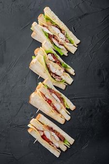 食材を使った新鮮なサンドイッチ、黒いテーブル、上面図