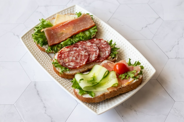 Fresh sandwiches with sausage, cheese, bacon, tomatoes, lettuce, cucumbers on marble