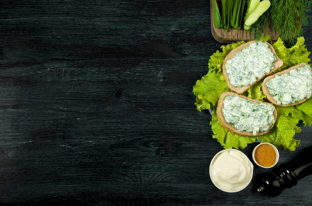 Fresh sandwiches with vegetables on a dark board