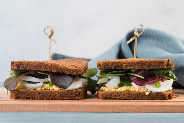 Fresh sandwiches on wooden board