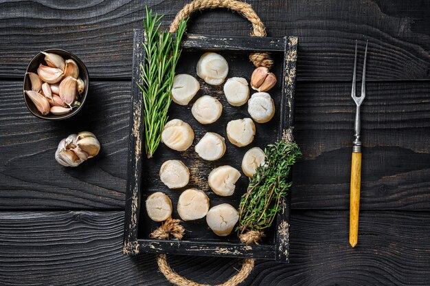木製のテーブルの上の木製トレイに新鮮なホタテの肉。上面図。