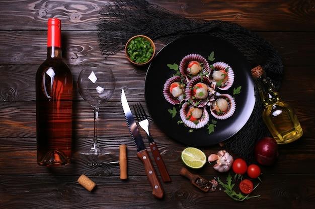Свежие гребешки с бутылкой розового вина со специями и овощами