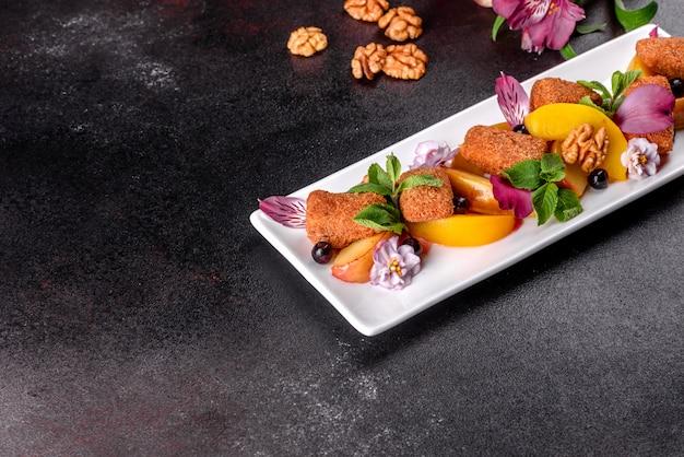暗いコンクリートの表面に白い皿に花で飾られた焼きリンゴと桃のフレッシュな香りのチーズスティック