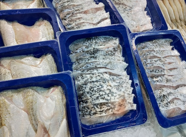 Fresh sea bass fish fillets packed in plastic trays ready for sale in supermarkets.