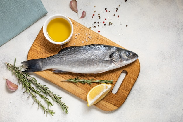 Fresh sea bass fish and ingredients for cooking, lemon and rosemary. white background top view.