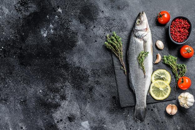 Свежая рыба морского окуня с зеленью и лимоном на черной тарелке. черный фон. вид сверху. скопируйте пространство.